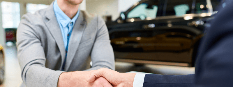 Men shaking hands at car showroom